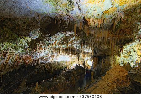 Scenic Landscape View Of Postojna Cave. Ancient Formations Inside Cave With Stalactites And Stalagmi