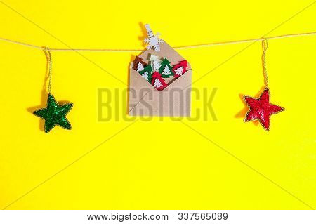 Christmas Card Concept. Craft Envelope With Felt Christmas Trees Figures Pined By Decorative Snowfla