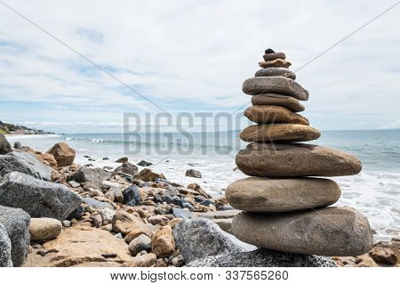 Balansed Stacked Stones Near The Ocean Water On The Beach