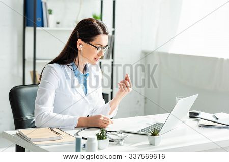 Female Positive Doctor In Earphones Having Online Consultation With Patient On Laptop In Clinic Offi