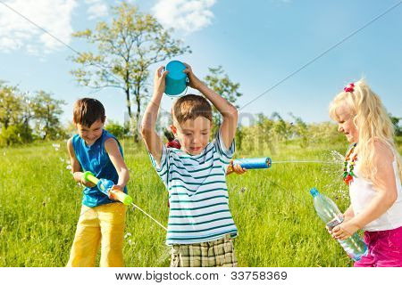 Soaked happy kids playing with water in the meadow