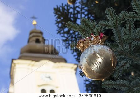 Golden Wrapped Christmas Balls Under The Pine Tree And Catholic Church Above It Under The Blue Sky|