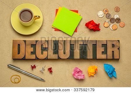 declutter - abstract in vintage letterpress wood type blocks with coffee, sticky notes, coins, pen, clear your workspace concept