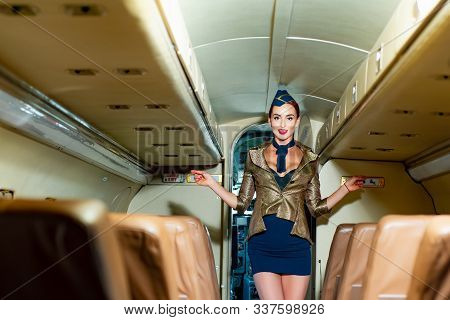 Attractive Young Woman Flight Attendant Stewardess. Portrait Of Smiling Flight Attendant Serving In