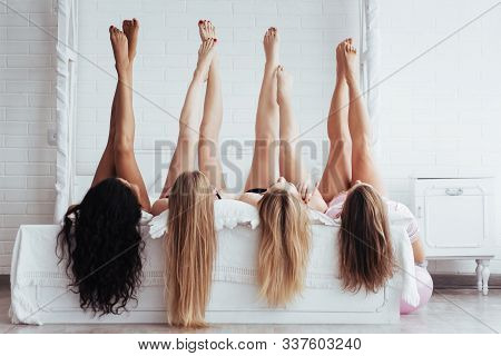 Different Skin Colors. Four Young Women With Good Body Shape Lying On The Bed With Their Legs Up.