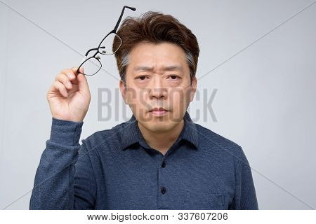 Asian Male Trying To Read Something In His Book. Poor Sight, Presbyopia, Myopia.