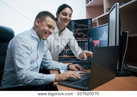 Team Of Stockbrokers Are Having A Conversation In A Office With Multiple Display Screens.