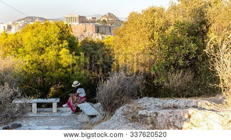 Asian Woman In White T-shirt In Athens In White Hat, Sitting On Marble Bench In Garden On Phillippas
