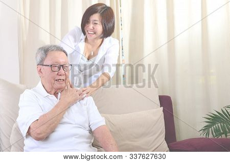 Asian Old Man Shoulder Pain, Sitting On Sofa , Daughter Massaging Father Shoulder. Chinese Family, S