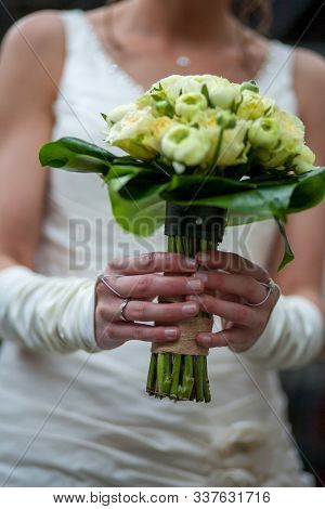 Unrecognizable Bride Wearing Her White Wedding Gown And Groom In A Black Suit With Bride Holding Wed