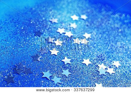 Silver Glitter And Stars On Blue Background. Blurry Glitter Texture. Sequin Texture.