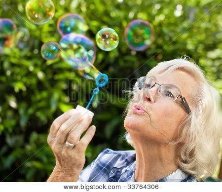 Senior woman is blowing bubbles in the garden,close-up
