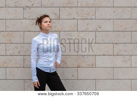 Attractive Woman In White Shirt Standing On Marble Brick Wall Background And Looking Ahead. Successf
