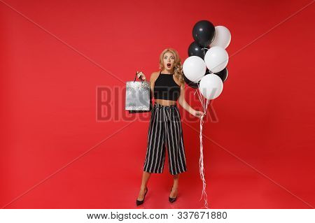 Shocked Woman Girl In Black Clothes Posing Isolated On Red Background. Shopping Discount Sale, Holid