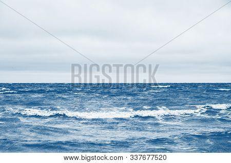 Classic Blue Sea Beach. North Sea. Stormy Weather: Strong Waves, Gloomy Sky, Sea Foam. Classic Blue