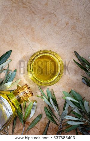 Extra Virgin Olive Oil In Glass Bowl. It Includes Olive Leaves And Branches. Rustic Background. Top