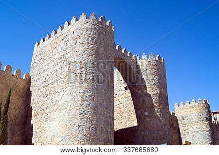 Historical City Walls At Avila, Northern Spain. A Fortified Gate With Towers And Battlements. Sturdy