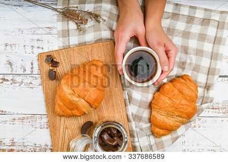 Girl Holds A Coffee Mug. On The Background Of A Croissant. Coffee With A Croissant. The Beginning Of