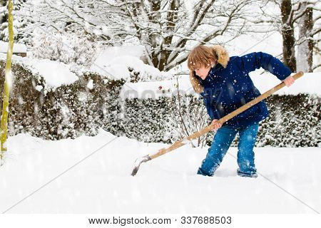 Child Shoveling Snow. Little Boy With Spade Clearing Driveway After Winter Snowstorm. Kids Clear Pat