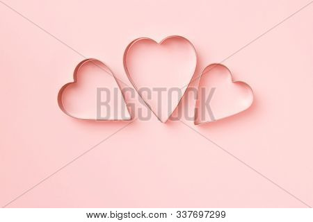 3 Cutters Cookies In Heart Shape On Pastel Pink Background. Concept Valentines Card. Top View, Copy