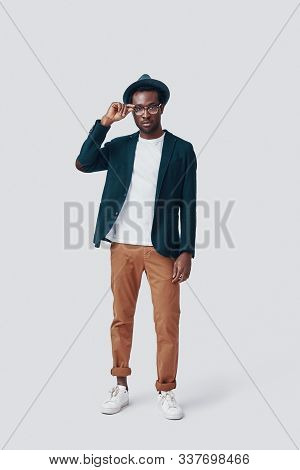Full Length Of Handsome Young African Man Looking At Camera And Adjusting His Eyewear While Standing