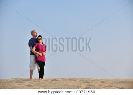 relaxed young pasionate couple enjoying the sunset  beauty on their honeymoon, on a desert with orange background