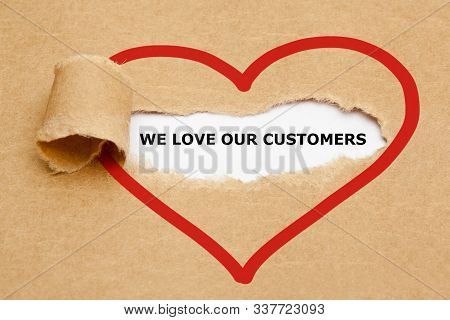 Text We Love Our Customers Appearing Behind Ripped Brown Paper.