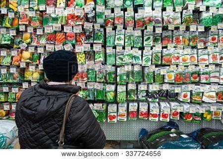 Minsk, Belarus - November 23, 2019: Woman Chooses Packed Seeds At Store For Gardener
