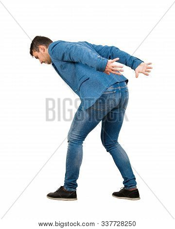 Bent Down Young Man Keeps Hands Back As Carrying An Heavy Invisible Object On His Shoulders Isolated