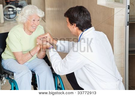 Young doctor comforting happy senior woman in hospital