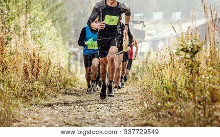 Group Runner Athletes Run Mountain Trail In Rain