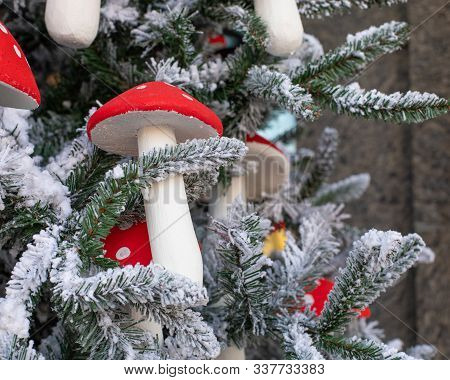 Artificial Mushroom Amanita Decorates A Christmas Tree. Amanita With A Red Hat Close-up. Snow-covere