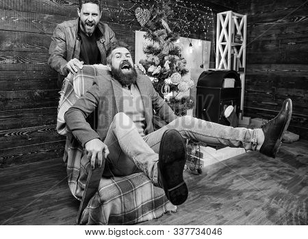 Best Friend Having Fun On Christmas Eve. Man Push Armchair With Friend. Cheerful Men Having Fun At H