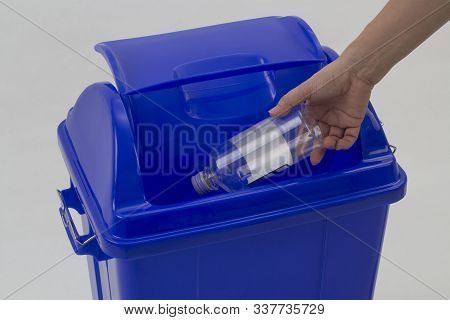 Woman Hand Holding Empty Bottle Into The Trash Isolated On White Background