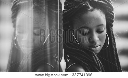 Portrait Of A Charming African Girl With Long Braids Leaning Against The Mirror Which Fully Reflects