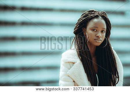 The Portrait Of A Charming Young African Female In A Demi-season Fur Coat, With Long Braids And Big