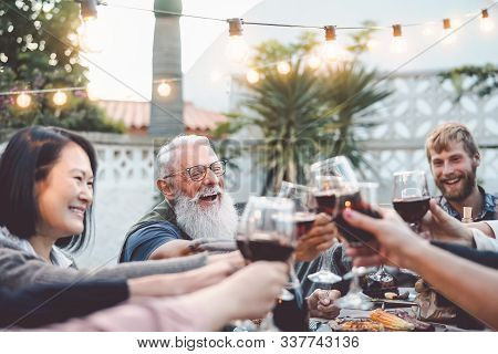 Happy Family Dining And Toasting Red Wine Glasses Outdoor - People With Different Ages And Ethnicity