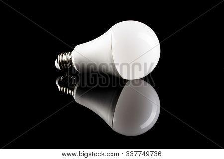 Energy saving light bulb on black table. LED light bulb.