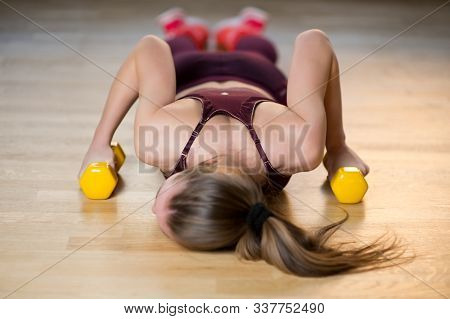 The Athlete Is Exhausted And Lies On The Floor In The Gym With Dumbbells In Her Hands, Selective Foc
