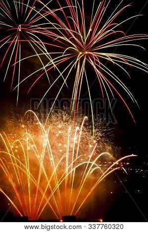 Colorful Fireworks On The Black Sky Background Over-water Golden