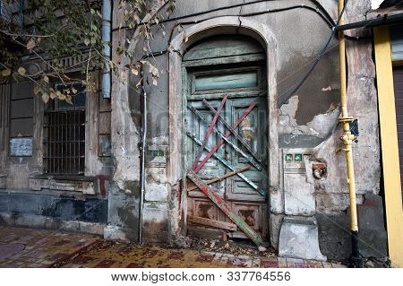 Boarded Up Wooden Door With An Arch Of An Old Abandoned Historic House And A Window With Bars