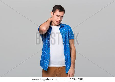 Unsure Man Stroking Neck Expressing Doubtful Emotion Isolated Over Grey Background.