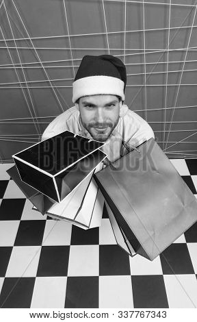 Man Santa Hold Bags On Black And White Checkered Floor. Shopper In Red Hat With Paperbags, Top View.