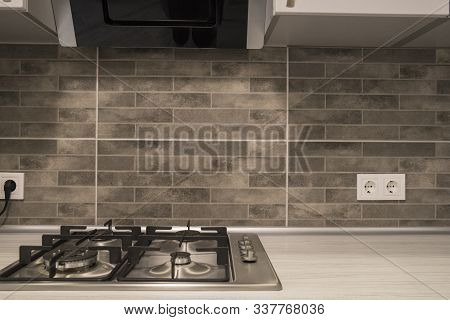 Modern Kitchen Interior With Stainless Steel Gas Cook-top And Grey Tile Backsplash