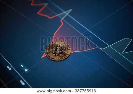 Conception Of New Era Of Currency. Picture Of Golden Bitcoin Lying On The Display With Graphs In Off