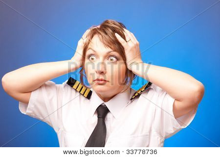 Worried woman pilot wearing uniform with epauletes looking ahead, standing on blue background.