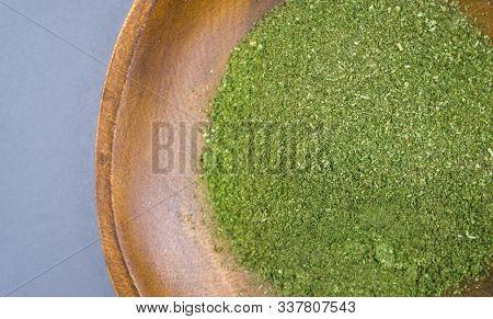 Coarse Grind Mitragynina Speciosa Or Kratom Powder In Wooden Bowl On Gray Background