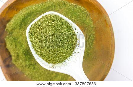 Coarse Grind Mitragynina Speciosa Or Kratom Powder In White Ceramic Spoon On Wooden Bowl