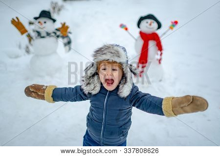 Happy Kid Winter Portrait. Kids In Snow. Happy Child Playing With A Snowman On A Snowy Winter Walk.