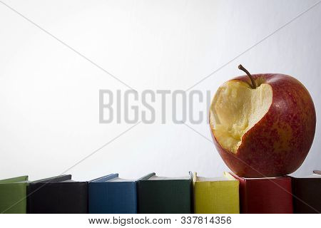 Apple And Books On A White Wall Background